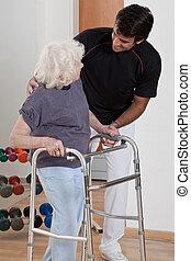 Therapeut, der Patienten hilft, Walker zu benutzen