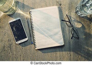 Top Aussicht auf einen alten Tisch mit Handy, Pad, Bleistift und Brille