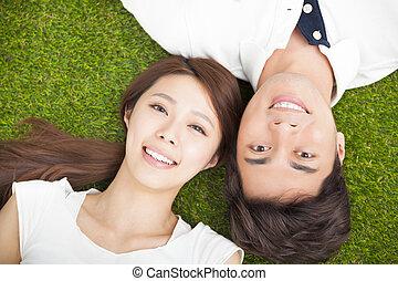 Top Aussicht auf junge Paare, die zusammen auf dem Rasen liegen.