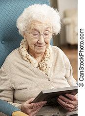 Traurige ältere Frau, die sich ein Bild ansieht