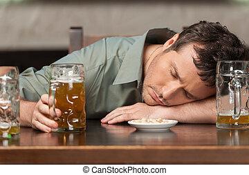 Trink verantwortungsvoll. Portrait von betrunkenen Männern, die mit geschlossenen Augen im Pub sitzen