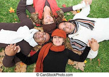 Umgekehrte Herbstgruppe glücklicher junger Menschen