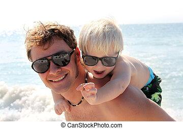 Vater, der ein glückliches Kind auf dem Schweinchen am Meer trägt.