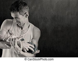 Vater mit Neugeborenem, im dunklen Hintergrund.