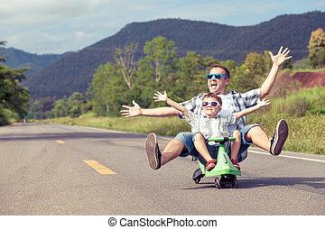 Vater und Sohn spielen auf der Straße.
