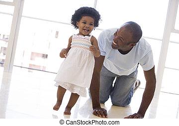 Vater und Tochter spielen drinnen und lächeln