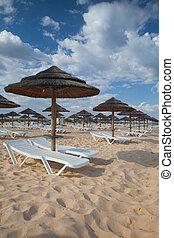 Verschiedene Sonnenschirme und Liegestühle am leeren Strand auf der Insel Tavira, Algarve. Portugal