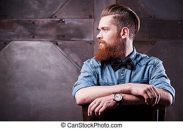 Vertraut in seinem perfekten Stil. Profil eines hübschen, jungen, bärtigen Mannes, der wegsieht und auf dem Stuhl sitzt