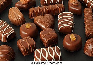 Viele Schokolade appetitlich mit Zuckerguss im dunklen Hintergrund