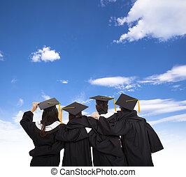 Vier Absolventen schauen in den Himmel