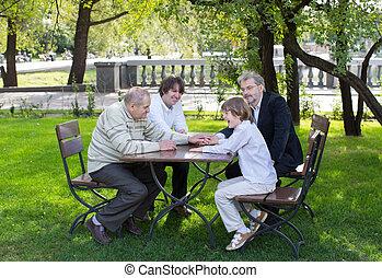 Vier Generationen Männer sitzen an einem Holztisch in einem Park, lachen und reden.