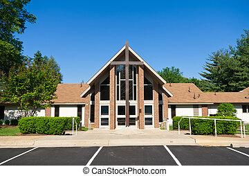 Vor der modernen Kirche mit großem Kreuz