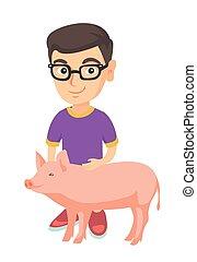 Weißer Bauernjunge mit Brille, der ein Schwein streichelt.