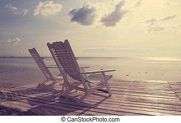 Weißer Holz-Strandstuhl mit Blick auf das Meer,vintage Filtereffekt.