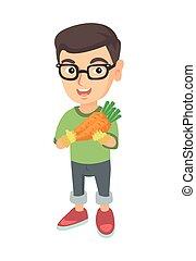 Weißer Junge mit Brille mit frischer Karotte.