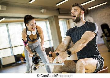 weibliche , gebrauchend, gesetzt, reihe, turnhalle, mann, trainer, maschine, junger, unterstuetzung