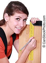 Weiblicher Schreiner, der Holz mit Set-Square markiert.