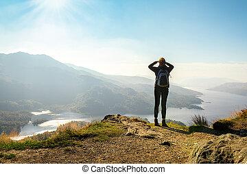 Weiblicher Wanderer auf dem Gipfel des Berges, der die Talansicht geniesst, ben a'an, loch katrina, highlands, scotland, UK.