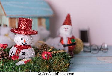 Weihnachtsschneemann, Weihnachtsmann und Geschenke, die auf grunge blauem Holzboden dekoriert sind.