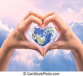 Welt in Herzform mit über Frauen menschliche Hände auf verschwommenen natürlichen Hintergrund: Weltherz Gesundheitstag, Aufnahme dieses Bild von der NASA eingerichtet.