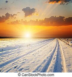 Winterlandschaft. Sonnenuntergang über der Straße mit Schnee