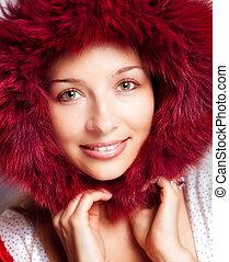 Winterporträt glücklicher Frau mit Pelzhaube.