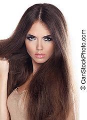 Wunderschöne Frau mit langen braunen Haaren. Bild von einem Modemodell, das im Studio posiert.