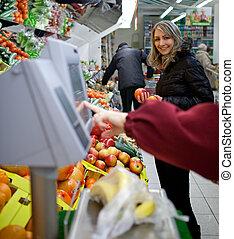 Wunderschöne junge Frau, die Obst und Gemüse in der Produktionsabteilung eines Lebensmittelgeschäftes/Supermarktes kauft.