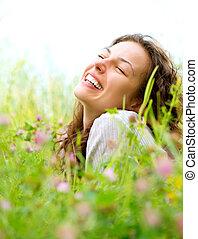Wunderschöne junge Frau liegt auf der Wiese der Blumen. Genießen Sie die Natur