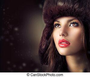 Wunderschöne junge Frau mit Pelzmütze. Winterstil