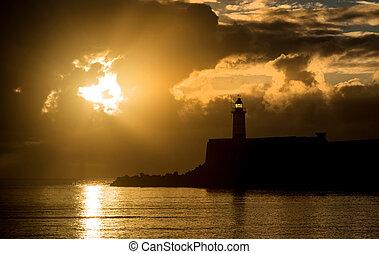 Wunderschöner, lebendiger Sonnenaufgang über ruhiges Wasser Ozean mit lightho.