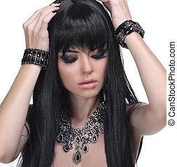 Wunderschönes Brünette-Mädchen. Gesundes langes Haar. Schmuck und Schönheit. Modefoto