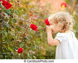 Wunderschönes Kind, das Rose riecht.