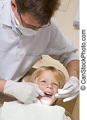Zahnarzt im Untersuchungsraum mit dem Jungen im Stuhl