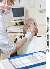 Zahnarzt im Untersuchungsraum mit Frau im Stuhl