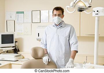 Zahnarzt im Untersuchungsraum mit Maske