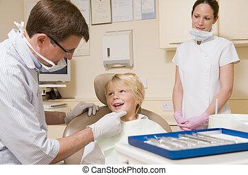 Zahnarzt und Assistent im Untersuchungsraum mit dem Jungen im Stuhl