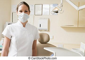 Zahnarztassistentin im Untersuchungsraum mit Maske