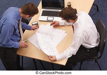 Zwei Architekten, die die Pläne durchsehen