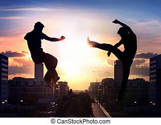 Zwei Capoeira-Kämpfer im Hintergrund der Stadt