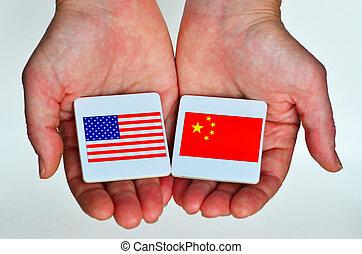 Zwei Hände halten die nationalen Flaggen der Vereinigten Staaten von Amerika (L) und der Republik China (R)