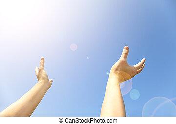 Zwei Hände mit geöffneten Handflächen halten nach oben zum blauen Himmel.