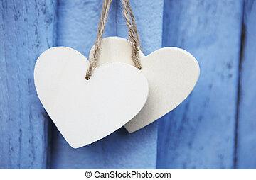 Zwei hölzerne Herzen hängen an der blauen Holzoberfläche