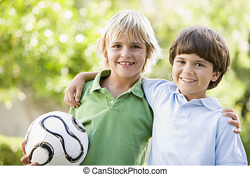 Zwei junge Jungs draußen mit einem Fußball-Lächeln