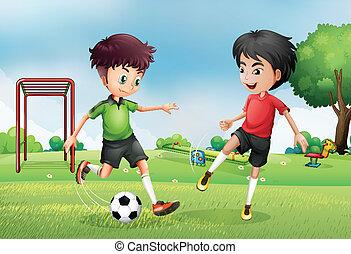 Zwei Jungs spielen Fußball in der Nähe des Parks