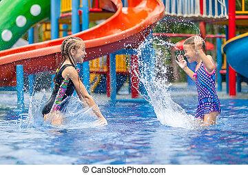 Zwei kleine Kinder spielen im Schwimmbad.