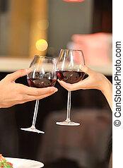Zwei Leute, die mit Weingläsern anstoßen. Das junge Paar trinkt Rotwein im Restaurant