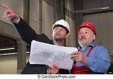Zwei Männer, die Pläne durchsehen und über Projekt reden