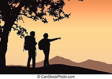 Zwei Touristen, die unter einem Baum stehen und in der Berglandschaft mit orangem Himmel und Platz für Ihren Text zeigen.